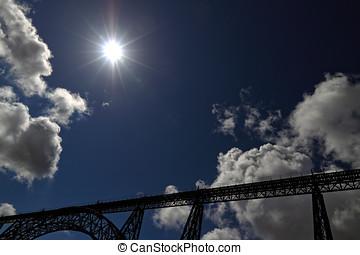 Backlit old iron bridge