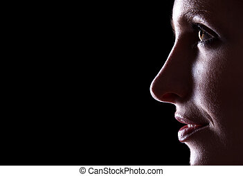 Backlit portrait of caucasian woman profile on black...
