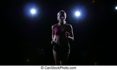 Backlit silhouette of a young woman running on a black...
