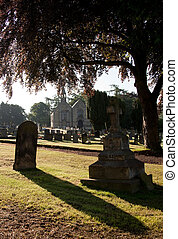 Backlit view of gravestones with church