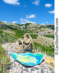 Backpack and map in mountain. nature composition.