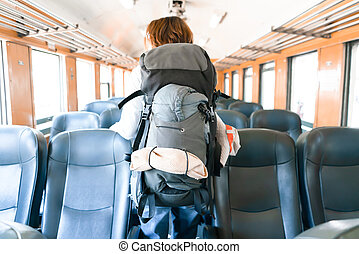 Backpack in the train with a traveler. Travel at Asia concept.