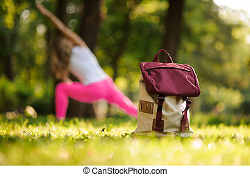 Backpack on grass in a green park on summer day against woman doing yoga