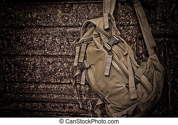 backpack hanging on a rusty wall at rest