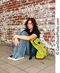 teen girl with backpack on sidewalk on city streets
