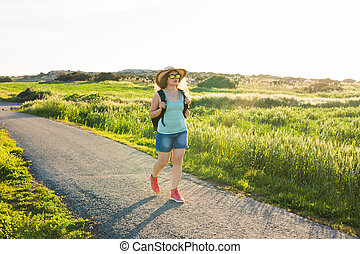 Backpack travel to European countryside, active lifestyle, active summer vacation concept - Woman traveler looking sunset at green field