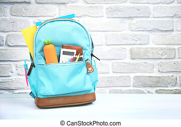 Backpack with school supplies and accessories empty space background.