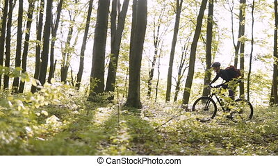Backpacked Man Rides Bicycle in the Forest