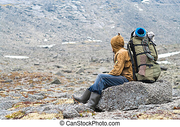 Backpacker a senior man sitting on rock in mountains