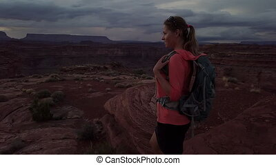 Backpacker Girl looks at the beautiful canyon vista island...