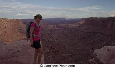 Girl walks along the Rim of East Fork Shafer Canyon near...