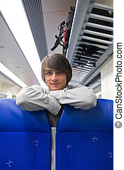 Backpacker in train - Backpacker leaning over the head rests...