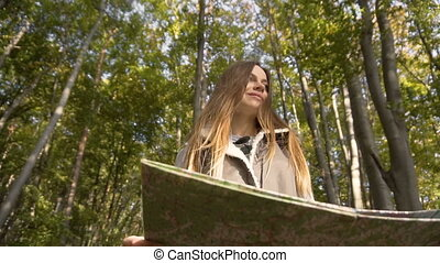 Backpacker Looks at Map in Forest