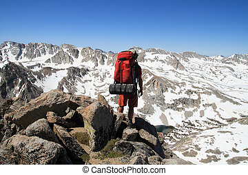 back view of a male backpacker looking down on Piute Pass in the Sierra Nevada Mountains from Mount Emerson