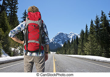 Backpacker on mountain road - Lonely backpacker looking at ...