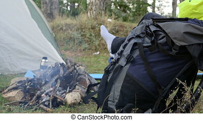 Backpacker sitting by campfire at campground