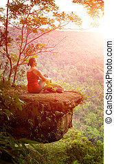 Backpacker sitting on the cliff high in mountains on the background of sunrise