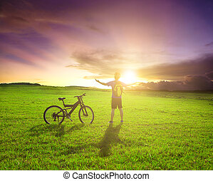 backpacker standing next to bicycle with sunset background