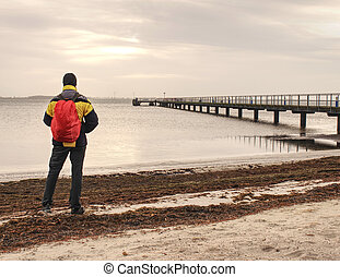 Backpacker tourist standing at sea on old wooden bridge.