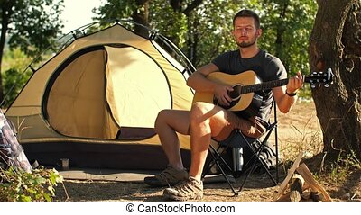 Backpacker with guitar at forest - Young man travel with...