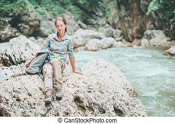 Backpacker woman sitting on the river bank.