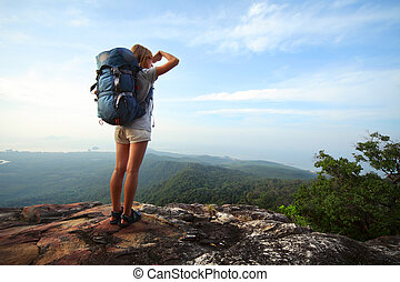 Backpacker - Young woman with backpack standing on cliff's ...