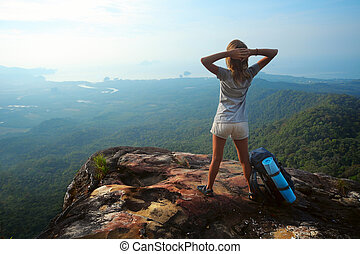 Backpacker - Young woman with backpack standing on cliff's...