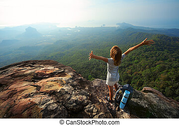 Young woman with backpack standing on cliff's edge and looking to a sky with raised hands