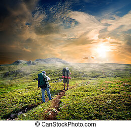 Backpackers on footpath in mountains at sunny day