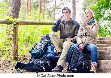 Backpackers taking rest and having mineral water