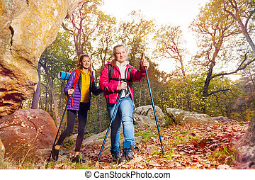 Backpackers with trekking poles walking on trail