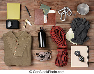 Overhead view of gear laid out for a backpacking trip on a rustic wood floor. Items include, rope, gloves, sweater, carabiners book, belt, cup, passport, wallet, canteen, compass, money, map, knife