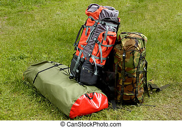 Backpacking time concept - backpacks ready for hiking standing on grass - summer vacation
