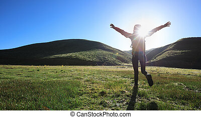 backpacking woman hiker hiking in sunrise mountains