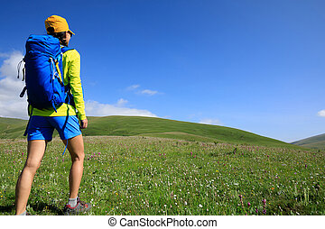 backpacking woman hiking in grassland mountain top
