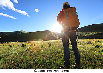 backpacking woman hiking in sunrise mountains