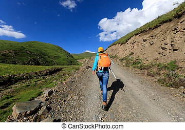 backpacking woman hiking on high altitude mountain trail