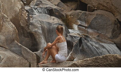 Backside Blond Girl Sits on Stone Looks at Waterfall