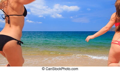 backside cheerleaders in colourful bikinis run into water