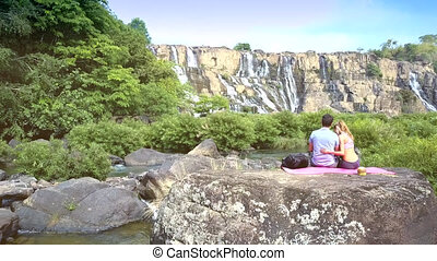 backside girl hugs guy on stone against waterfall