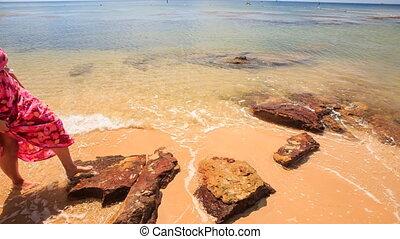 Backside Girl in Long Walks Barefoot along Sea on Sand Beach