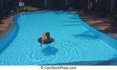 backside girl lies on inflatable ring in pool