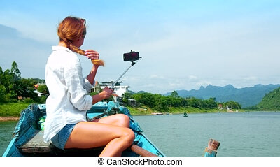 backside girl with long plait makes selfie on boat bow -...