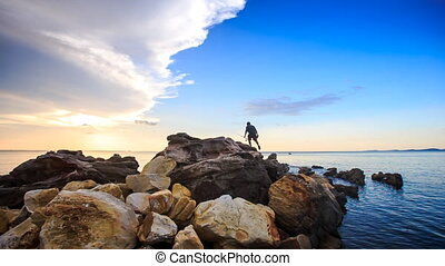 Backside Guy with Rods Walks on Stones to Sea at Sunset
