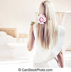 Backside portrait of a blond lady in a luxurious apartment