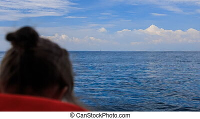 backside view girl looks into distance of sea from nose of...