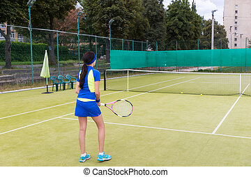 Backside view of beautiful sporty girl playing tennis