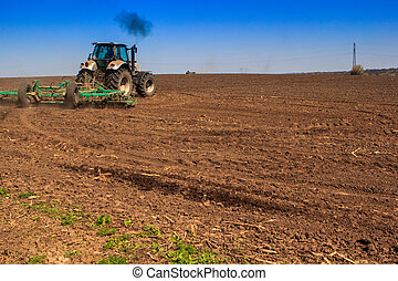 backside view of tractor sowing in field in spring