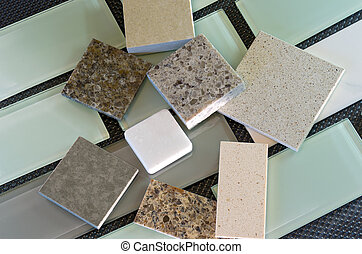 Glass subway tile samples used in kitchen backsplashes and quartz samples for countertops