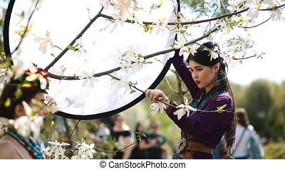 Backstage of ethnic photoshoot outdoor. - Young woman keep...